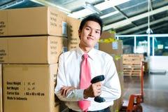 Homem novo em um armazém com varredor Imagens de Stock