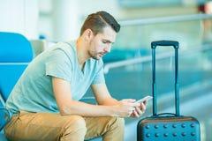 Homem novo em um avião de espera do voo da sala de estar do aeroporto Homem caucasiano com o smartphone na sala de espera Fotos de Stock Royalty Free