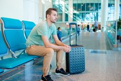 Homem novo em um avião de espera do voo da sala de estar do aeroporto fotos de stock