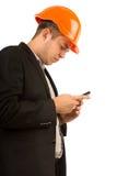 Homem novo em um capacete de segurança que lê uma mensagem de texto Foto de Stock