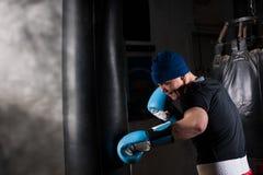 Homem novo em um chapéu e em luvas de encaixotamento que treina com punchi do encaixotamento Imagem de Stock