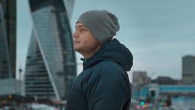 Homem novo em um chapéu que olha longe na perspectiva dos arranha-céus filme