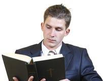 Homem novo em um estudo da Bíblia do terno Foto de Stock