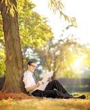 Homem novo em um jornal da leitura da grama em um parque em um dia ensolarado Imagem de Stock