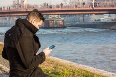 Homem novo em um revestimento preto do inverno que senta-se no Riverbank e no Lo Foto de Stock