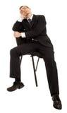 Homem novo em um terno de negócio preto que senta-se em um ch Fotografia de Stock