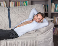 Homem novo em um terno que encontra-se no sofá Foto de Stock