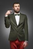 Homem novo em um terno verde, apontando no direito imagem de stock