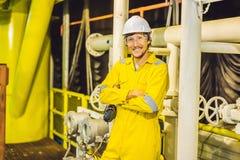 Homem novo em um uniforme amarelo, em vidros e em capacete do trabalho na planta de ambiente industrial, de plataforma petrol?fer imagem de stock