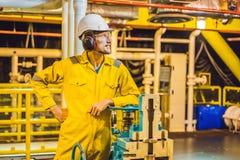 Homem novo em um uniforme amarelo, em vidros e em capacete do trabalho na planta de ambiente industrial, de plataforma petrol?fer foto de stock