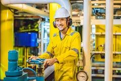 Homem novo em um uniforme amarelo, em vidros e em capacete do trabalho na planta de ambiente industrial, de plataforma petrol?fer fotos de stock