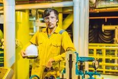 Homem novo em um uniforme amarelo, em vidros e em capacete do trabalho na planta de ambiente industrial, de plataforma petrol?fer foto de stock royalty free