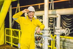 Homem novo em um uniforme amarelo, em vidros e em capacete do trabalho na planta de ambiente industrial, de plataforma petrol?fer imagens de stock