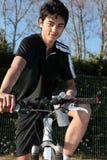 Homem novo em uma bicicleta de montanha fotografia de stock