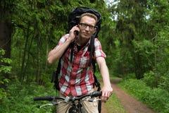 Homem novo em uma bicicleta que fala na floresta em um telefone celular Imagem de Stock