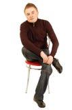 Homem novo em uma cadeira Fotografia de Stock Royalty Free