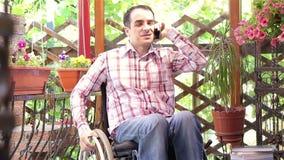 Homem novo em uma cadeira de rodas que fala no telefone filme