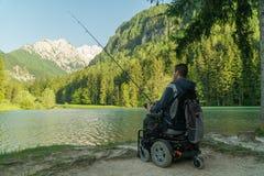 Homem novo em uma cadeira de rodas que pesca no lago bonito em um dia ensolarado, com as montanhas na parte traseira foto de stock