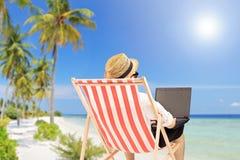 Homem novo em uma cadeira exterior que trabalha em um portátil, em uma praia Imagem de Stock