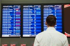 Homem novo em uma camisa com uma mala de viagem no aeroporto perto do calendário do voo fotografia de stock royalty free