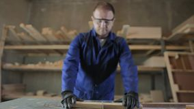 Homem novo em uma fábrica da mobília que corta as partes de madeira para o sofá filme