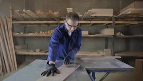 Homem novo em uma fábrica da mobília que corta as partes de madeira para o sofá vídeos de arquivo