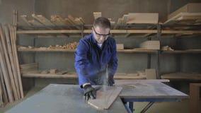 Homem novo em uma fábrica da mobília que corta as partes de madeira para o sofá video estoque