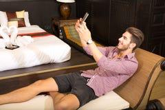 Homem novo em uma sala de hotel que toma um selfie Fotografia de Stock Royalty Free
