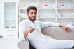 Homem novo em uma televisão de observação do roupão em casa em um sofá co imagem de stock royalty free