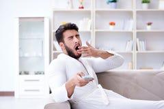Homem novo em uma televisão de observação do roupão em casa em um sofá co imagem de stock