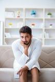 Homem novo em uma televisão de observação do roupão em casa em um sofá co imagens de stock royalty free