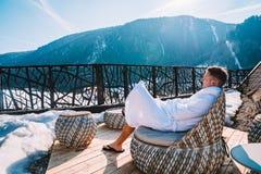 Homem novo em uma veste que refrigera em um terraço aberto Fotografia de Stock
