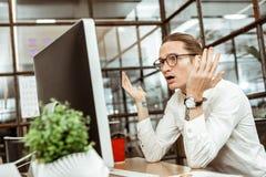 Homem novo emocional que olha o tela de computador foto de stock