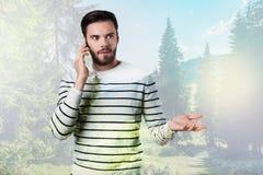 Homem novo emocional que olha surpreendido ao falar no telefone foto de stock