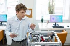 Homem novo encantador observando o mecanismo da impressora 3D Fotos de Stock Royalty Free