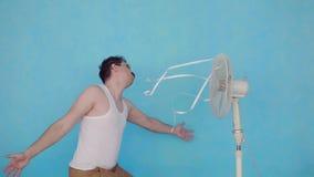Homem novo engraçado com o fã elétrico que aprecia o vento fresco no fundo azul vídeos de arquivo