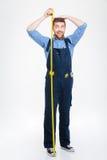 Homem novo engraçado feliz que mede sua altura do corpo usando a fita imagens de stock