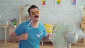 Homem novo engraçado na frente dos escapes de trabalho de um fã elétrico do calor no apartamento video estoque