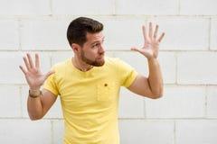 Homem novo engraçado na parede de tijolo com as mãos abertas que olham o rightsi Fotografia de Stock
