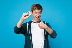 Homem novo engraçado na roupa ocasional que mostra o polegar acima, guardando o bitcoin, moeda futura isolado no fundo azul da pa foto de stock royalty free