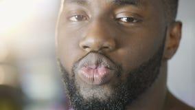 Homem novo engraçado que faz o ar beijar e que sorri na câmera, indivíduo que flerta com meninas filme