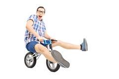 Homem novo engraçado que monta uma bicicleta pequena Fotos de Stock