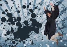 Homem novo entusiasmado do estudante que salta e que mantém um diploma contra o fundo chapinhado azul Imagens de Stock