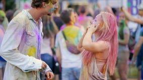 Homem novo entusiasmado e mulher cobertos nas cores de Holi, dançando na multidão no concerto vídeos de arquivo