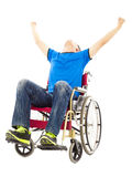 Homem novo entusiasmado que senta-se em uma cadeira de rodas e que levanta as mãos Fotografia de Stock Royalty Free