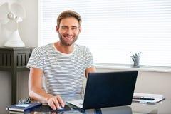 Homem novo esclarecido da tecnologia que sorri na câmera que senta-se atrás do computador foto de stock