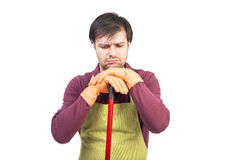 Homem novo esgotado com o avental cansado a limpar Imagens de Stock