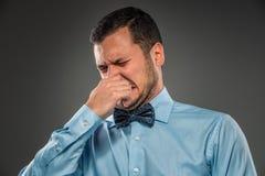 Homem novo - expressão enojado que fecha suas narinas com finge Imagens de Stock