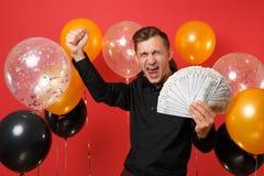 Homem novo extático na camisa clássica que faz o gesto do vencedor, guardando lotes do pacote dos dólares, dinheiro do dinheiro n fotos de stock