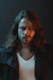 Homem novo farpado à moda considerável com o cabelo longo que olha para baixo no estúdio Imagem de Stock Royalty Free